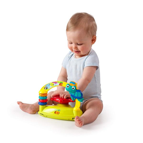 Infant playing with toy station