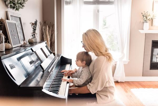 Mom teaching her kid to play piano